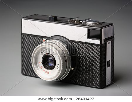 White metal and black plastic old-fashioned camera, isolated over white