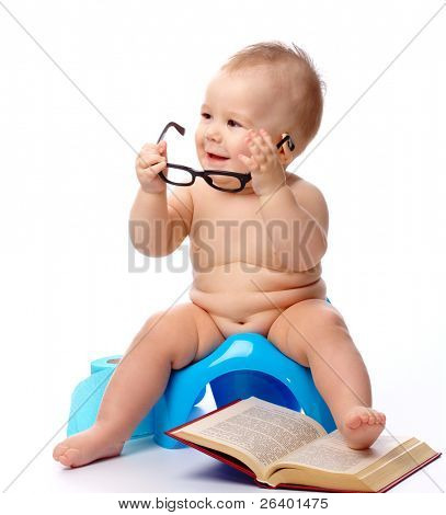 Child on potty play with glasses and book, isolated over white