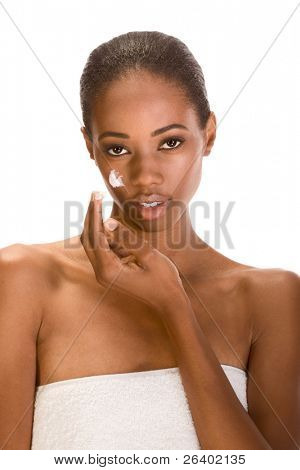 Beautiful young ethnic woman with Slicked Back Hair wrapped in white bath towel applying moisturizer on her face
