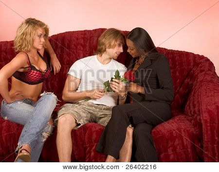 ethnic woman tries to seduce young Caucasian man while his girlfriend disapprovingly observes the scene.