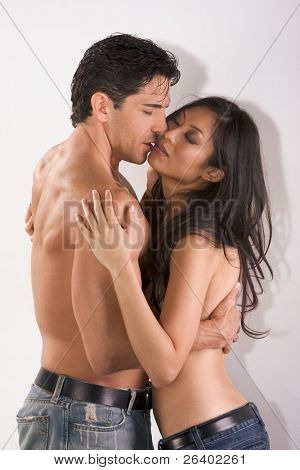 Loving affectionate nude multiethnic heterosexual couple in affectionate sensual kiss. Mid adult Caucasian men in late 30s and young black African-American woman in 20s