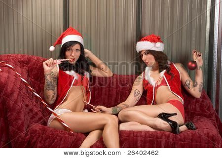 Two sexy seductive women in Christmas Mrs Santa Claus outfits, hats and lingerie in love