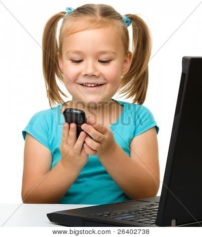 Cute little girl is sitting at table with her black laptop and a cell phone, isolated over white