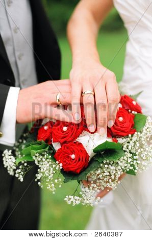 two hands on a bride bouquet