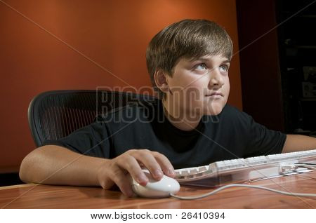 Tween boy working or playing in front of computer monitor
