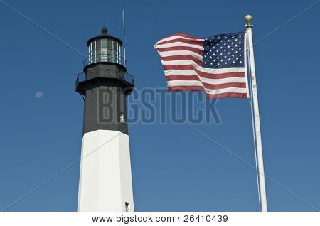 Tybee black and white navigational lighthouse in Georgia GA with USA flag