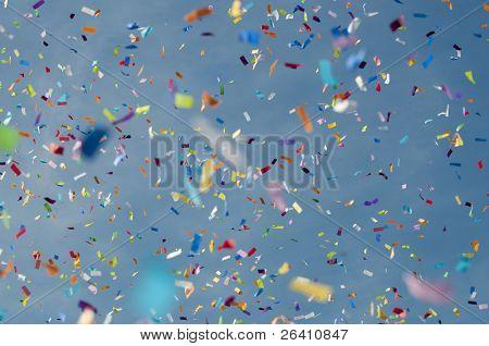 Festive colorful confetti against blue sky background
