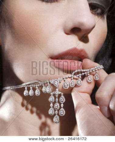 A sexy woman playing with her diamond necklace