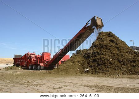 a mulching machine dumps into a pile of mulch