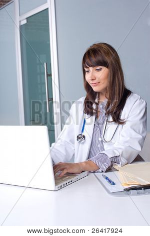 Woman doctor in a modern office at a desk with a laptop