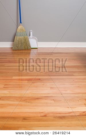 A Corn Broom on New Hardwood Flooring with a dust pan