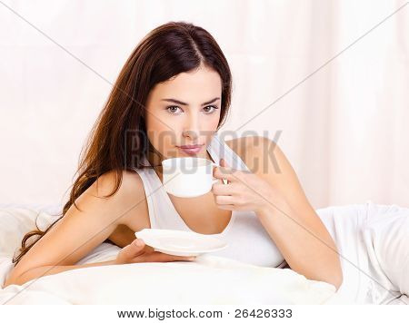 Woman Holding Cup Of Coffee In Bed