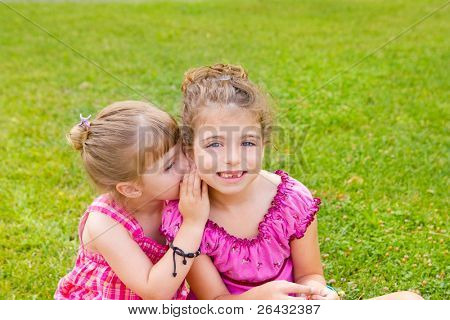 children girl sister friends whispering ear in green grass park
