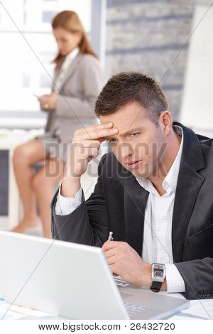 Businessman working on laptop in bright office, woman texting in background.?