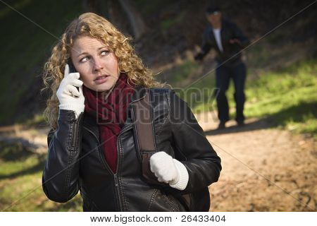 Pretty Young Teen Girl Calling on Cell Phone with Mysterious Strange Man Lurking Behind Her.