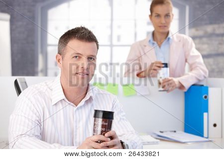 Casual office workers having break in office, drinking coffee.?