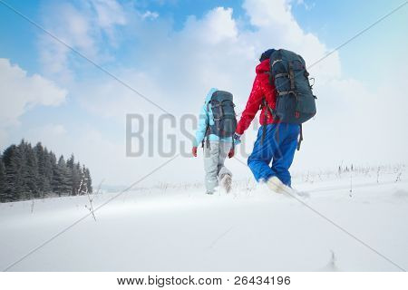 Backpackers walking through deep snowy field near forest
