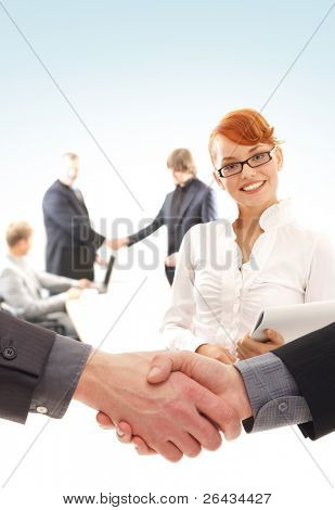 Young redhead businesswoman in front and some businesspeople behind