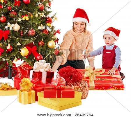 Happy family in Santa hat with child near Christmas tree.  Isolated.