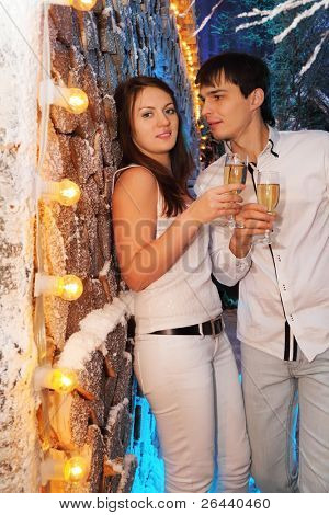 Young man and woman wearing white shirts with glasses of champagne stand near stack of wood