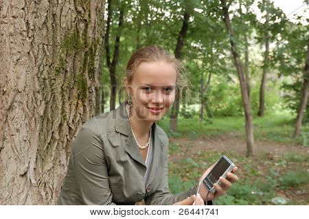 Beautiful girl sitting on a park with smile, with computer