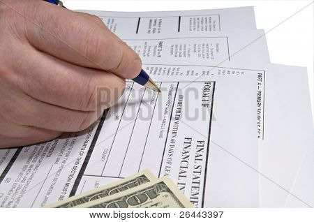 Hand filling income tax form with pen