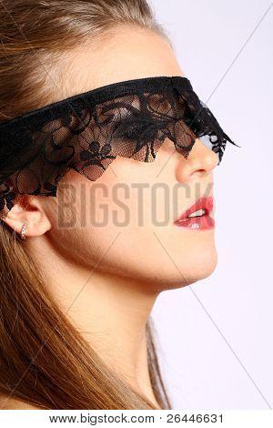 Mulher bonita com máscara de renda preta sobre o rosto