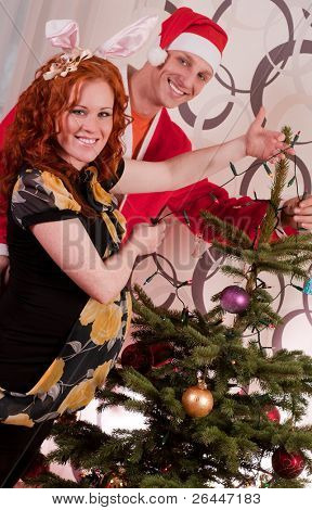 Young happy couple decorating a Christmas tree