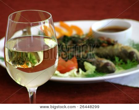 Glass of white wine with fried fish on background