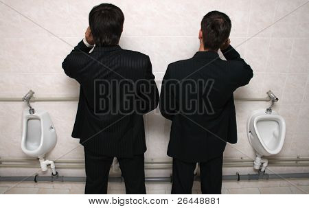 Two businessman talking by mobile phones in a WC