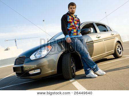 Young man holding keys of his new car