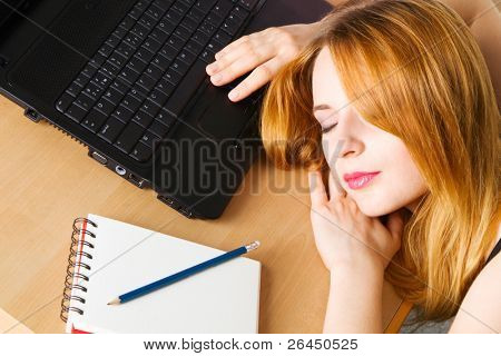 Young woman sleeping at her workplace
