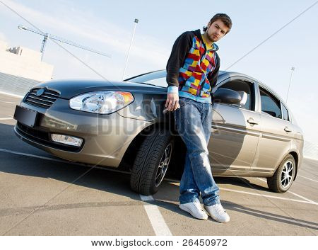 Handsome man standing near his new car