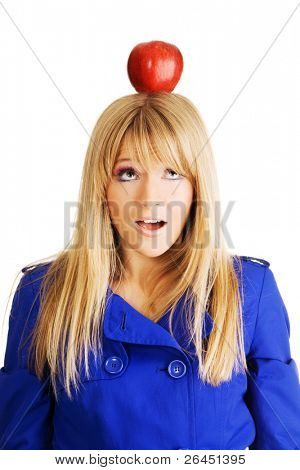 Funny frightened young woman with an apple on her head