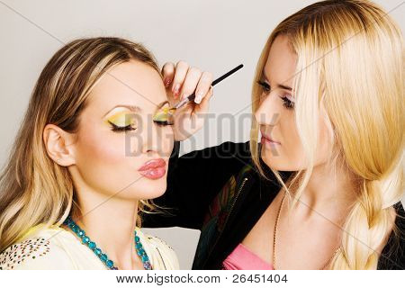 Professional visagiste applying makeup to a model