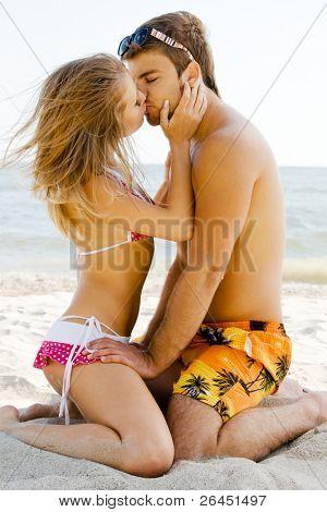 Beautiful couple kissing on the sea shore