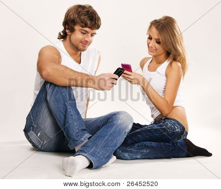 Beautiful couple with mobile phones studio photo