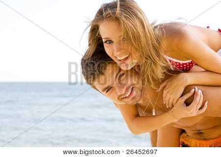 Beautiful young couple having fun on the seaside