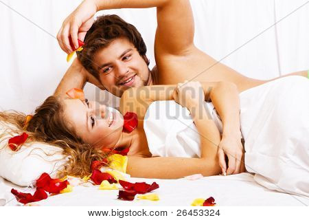 Beautiful couple in rose petals in bedroom