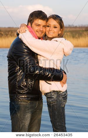 Young beautiful couple having fun on a river bank