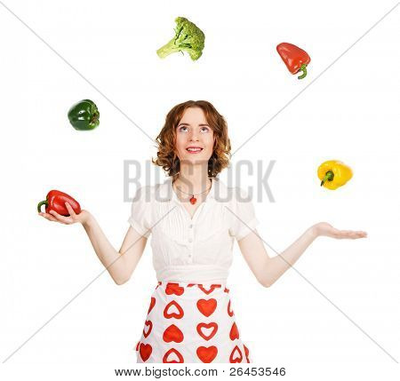 Young beautiful woman juggling with vegetables, white background