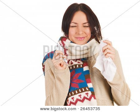 Cute young woman sneezing, with nose spray and handkerchief in her hands