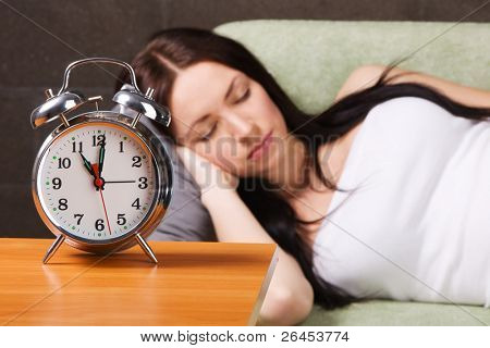 Vintage alarm clock, with beautiful young woman sleeping in the background