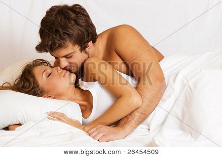 Young beautiful couple kissing in bed