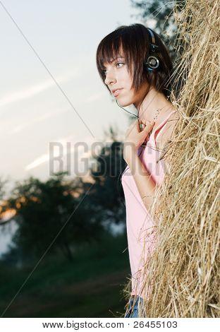 Lovely girl in headphones listening a music outdoors