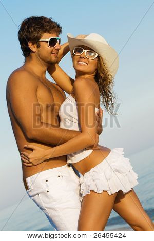 Young beautiful couple on a sea shore, focus on woman