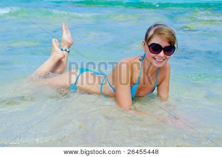 Beautiful Young Woman In Bikini Lying Down And Smiling In Sea