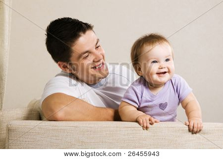 Happy young father with his little daughter having fun at home