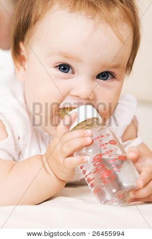 Cute baby drinking water and looking at the camera