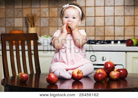 Little girl on table at kitchen eating an apple